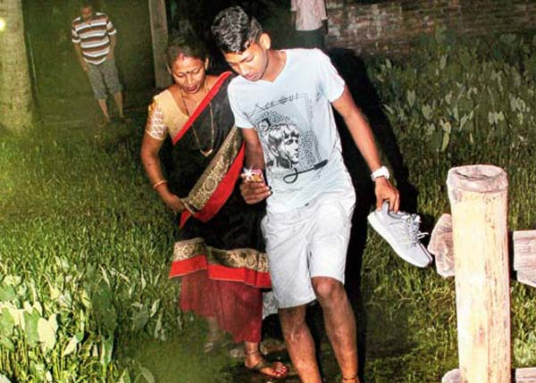 জল-কাদা ভেঙে বাড়িতে ঢুকছে বিশ্বকাপ খেলে আসা রহিম আলি। সঙ্গে মা সীমা বেগম। ইছাপুর বিবেকনগরে। ছবি: সজল চট্টোপাধ্যায়।