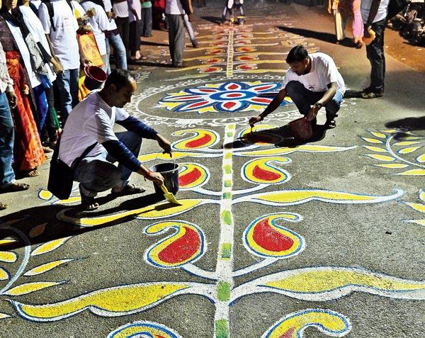 রং-রুট: আলপনায় ব্যস্ত শিল্পীরা। শনিবার রাতে ফুলিয়ায়। ছবি: সুদীপ ভট্টাচার্য