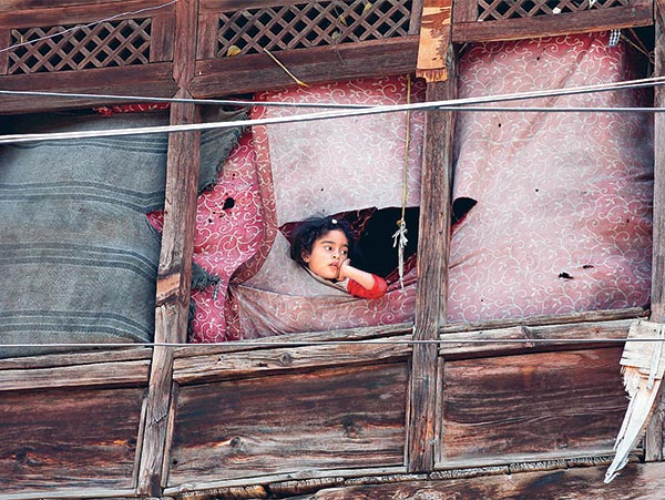 উঁকি: বাইরে তখন চলছে পুলিশ ও বিক্ষোভকারীদের সংঘর্ষ। সেই হিংসার সাক্ষী এই খুদেও। শনিবার শ্রীনগরে। ছবি: পিটিআই।