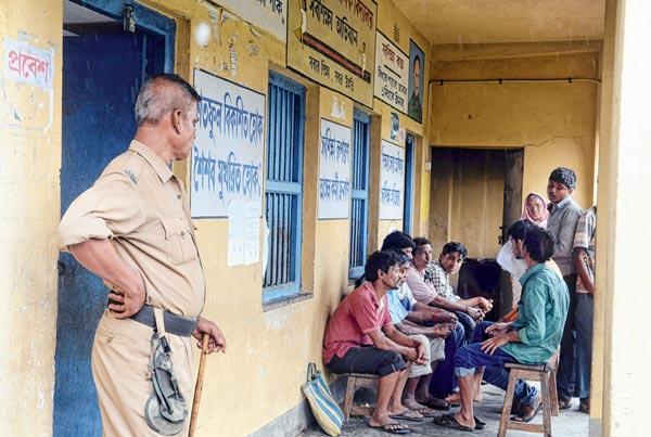 বুথের বারান্দায় পুলিশের সামনেই বসে বহিরাগতরা, পাঁশকুড়ার ভবানীপুর প্রাথমিক বিদ্যালয়। ছবি: পার্থপ্রতিম দাস
