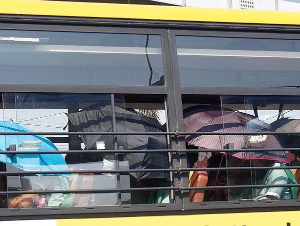 আড়াল: দুপুরের চড়া রোদ থেকে বাঁচতে বাসের মধ্যেও ভরসা ছাতাই। বৃহস্পতিবার দুপুরে, দক্ষিণ কলকাতায়। ছবি: সুমন বল্লভ