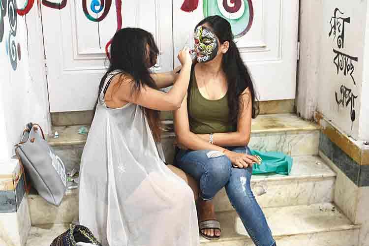 সাজ: বডি আর্টের স্টলে রং-তুলি হাতে ব্যস্ত শিল্পী। সোমবার, প্রেসিডেন্সি বিশ্ববিদ্যালয়ে। ছবি: সুমন বল্লভ