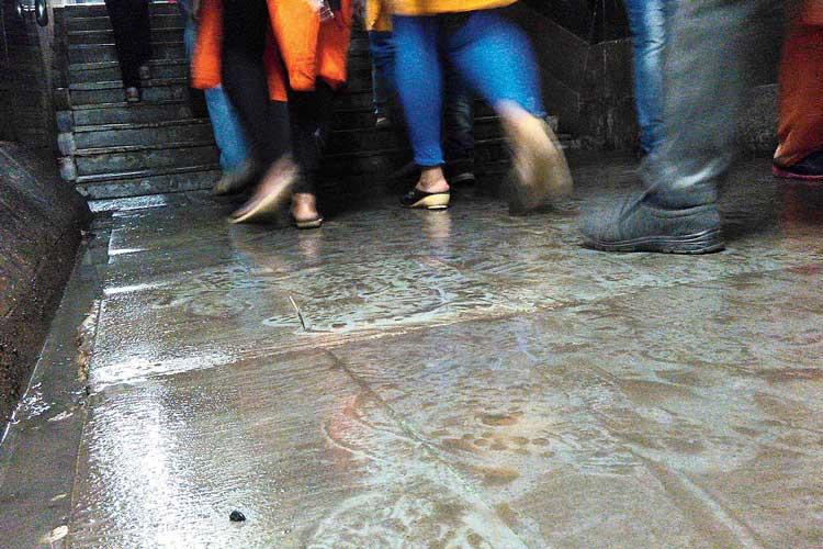 দুর্ভোগ: পাম্প চালিয়ে জল বার করার পরে ফের তা ব্যবহার করছেন যাত্রীরা। রবিবার, সোদপুর স্টেশনের সাবওয়েতে। ছবি: সজল চট্টোপাধ্যায়