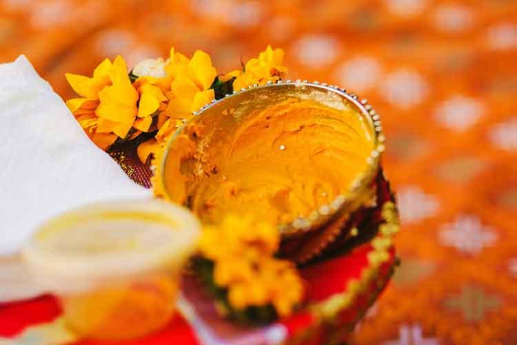 কাঁচা হলুদ বেটে বর-কনের গায়ে মাখানো হিন্দু বিয়ের অন্যতম রীতি। ছবি: শাটারস্টক।