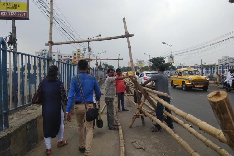 টালাসেতুর দু'পাশে বাঁশের ব্যারিকেড করে রাস্তার পরিসর কমানো হচ্ছে—— নিজস্ব চিত্র