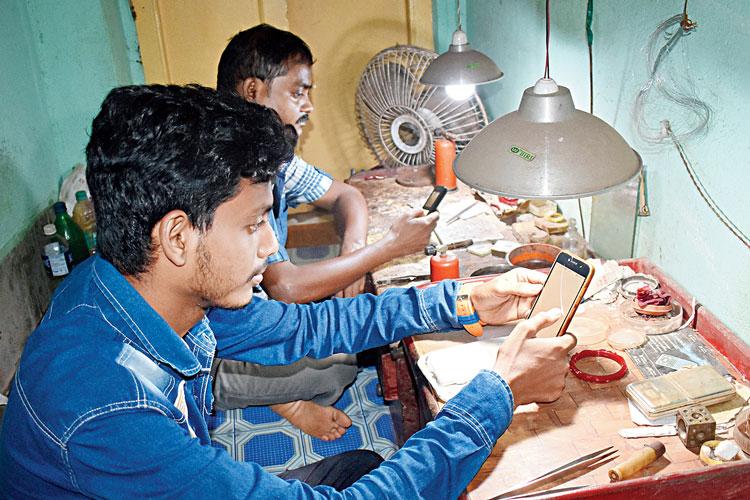 সোনার কাজ নেই। মোবাইলে ডুবে কারিগরেরা। ছবি: কৌশিক সাঁতরা