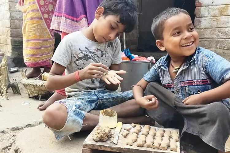 আউশগ্রামের দ্বারিয়াপুরে ডোকরাপাড়ায় কাদা-মাটি নিয়ে ব্যস্ত দুই খুদে। ছবি: প্রদীপ মুখোপাধ্যায়