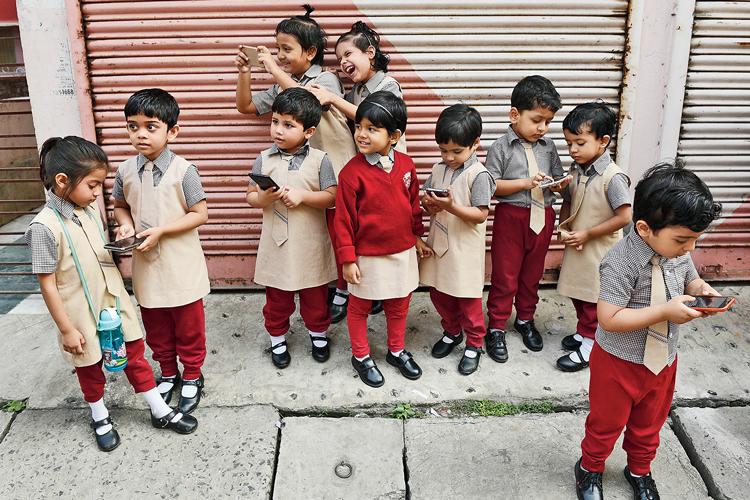 মুঠোভরে: স্কুল থেকে বেরিয়ে মোবাইলে বুঁদ খুদেরা। ছবি: সুমন বল্লভ