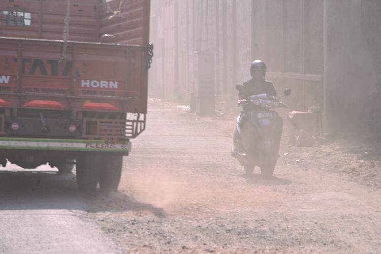 ঝাপসা: ভাঙা রাস্তার ধুলোয় ঢেকেছে হাওড়ার জে এন মুখার্জি রোড। ছবি: দীপঙ্কর মজুমদার