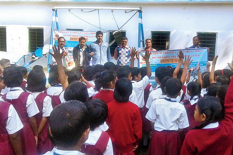 প্রচার: তীর্থভারতী স্কুলে পড়ুয়াদের সঙ্গে আরপিএফ এবং জিআরপি-র আধিকারিকেরা। বৃহস্পতিবার। ছবি: সজল চট্টোপাধ্যায়