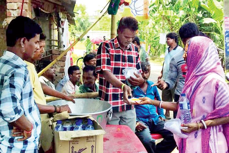 স্বাদ-বদল: বিজেপির বুথ কার্যালয় থেকে ভোটারদের বাতাসা-জল বিলি। সোমবার দুপুরে পান্ডুয়ার বেলুন গ্রামে নিজস্ব চিত্র