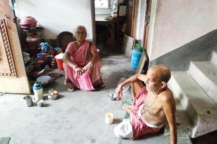 অসহায়: ঘরে পড়েছে তালা। বারান্দায় পড়ে বৃদ্ধ দম্পতি। নবদ্বীপের চর স্বরূপগঞ্জে। নিজস্ব চিত্র