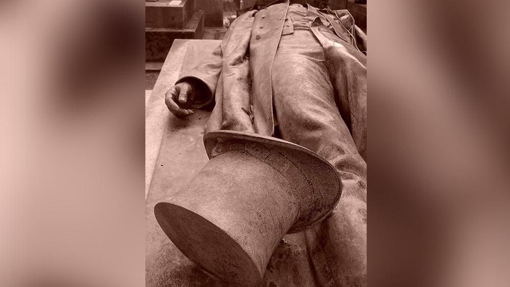 এক ফরাসি সাংবাদিকের কবর। সদা জাগ্রত সাংবাদিক যেন শুয়েও জেগে রয়েছেন।