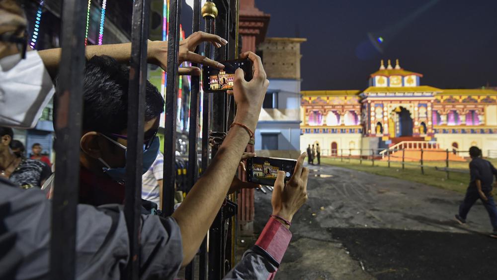 কলকাতা হাইকোর্টের রায়ে পুজো প্যান্ডেল চত্বরে নো এন্ট্রি জোন। তার মধ্যেই দূর থেকে দর্শকদের উঁকিঝুঁকি। ছবি: পিটিআই