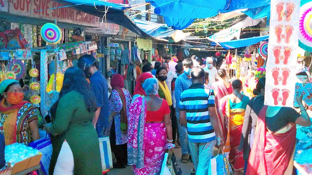 বিধিভঙ্গ: দূরত্ব বিধি উড়িয়ে লক্ষ্মীপুজোর বাজারে ভিড়। বুধবার জলপাইগুড়ি শহরে। ছবি: সন্দীপ পাল।