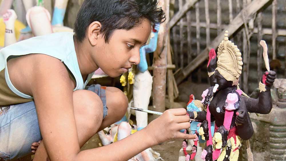 খুদে কালী বানাতে ব্যস্ত খুদে শিল্পী। বালুরঘাটে। ছবি: অমিত মোহান্ত