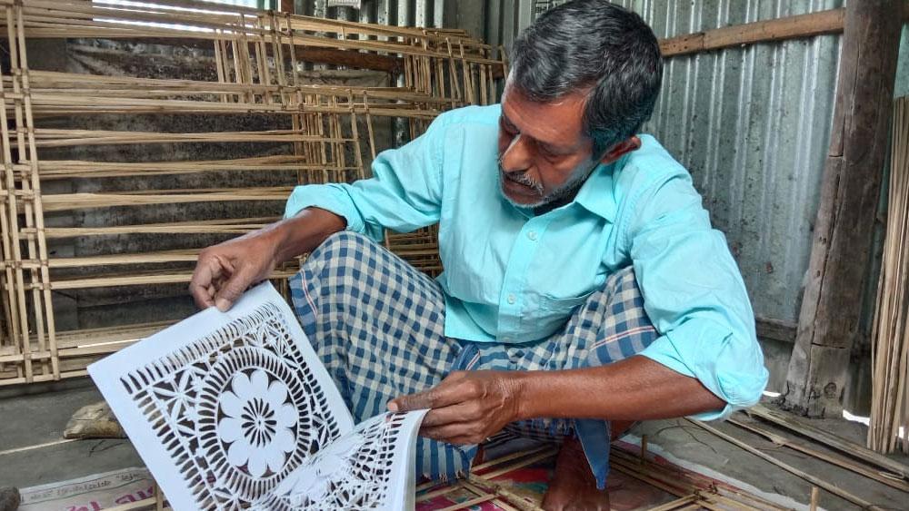 আলতাফ মিঞাঁ। রাসচক্রক তৈরির কাজ করছেন। নিজস্ব চিত্র।
