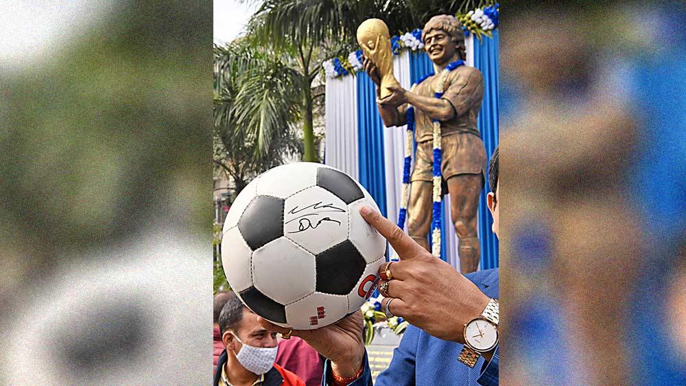 স্মৃতি: মারাদোনার সই করা ফুটবল নিয়ে তাঁর মূর্তির সামনে। বৃহস্পতিবার, লেক টাউনে এক অনুষ্ঠানে। ছবি: সুমন বল্লভ