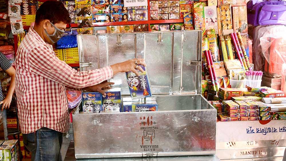গুটিেয়: বিক্রি বন্ধ। সাজিয়ে রাখা বাজি বাক্সে ভরে ফেলছেন এক ব্যবসায়ী। বাঁকুড়ার চকবাজারে শনিবার। ছবি: অভিজিৎ সিংহ