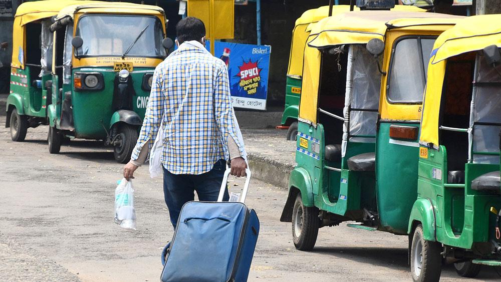 বাস না পেয়ে অটো ধরতে যাচ্ছেন এক যাত্রী। সোমবার দুর্গাপুরে সিটি সেন্টার বাসস্ট্যান্ডে। ছবি: বিশ্বনাথ মশান