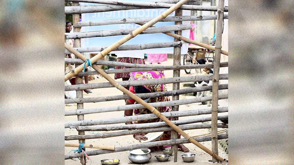 দূরত্ব: ব্যারিকেডের বাইরে থেকে খাবার রেখে যাচ্ছেন আত্মীয়েরা। শনিবার পুরুলিয়া শহরের ভুঁইয়াপাড়ায়। ছবি: সুজিত মাহাতো