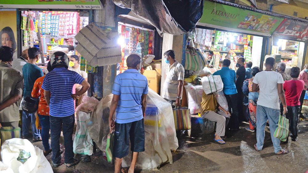 জমজমাট: কিছু এলাকায় ফের চালু হবে লকডাউন, ঘোষণার পরে ভিড় মুদির দোকানে। বুধবার, বারাসতের বড়বাজার এলাকায়। ছবি: সুদীপ ঘোষ