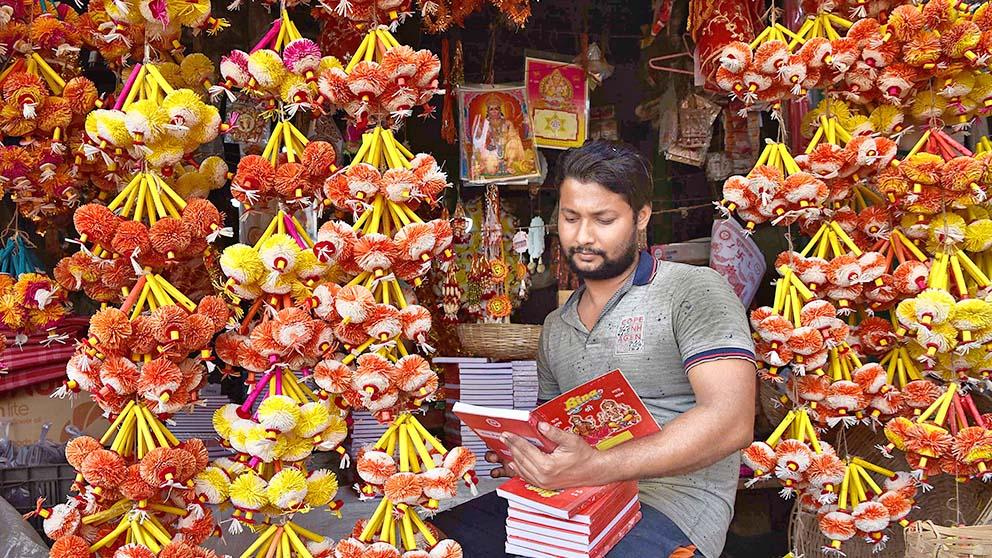 আহ্বান: নতুন বছরের সূচনার আগে এক দোকানি। বুধবার, উত্তর কলকাতায়।