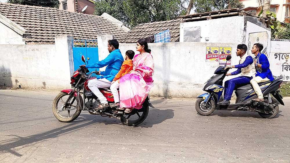 মুখে নেই মাস্ক। মাথায় হেলমেট ছাড়াই সওয়ার মোটরবাইক, স্কুটিতে। মঙ্গলবার কালনার রাস্তায়। নিজস্ব চিত্র।