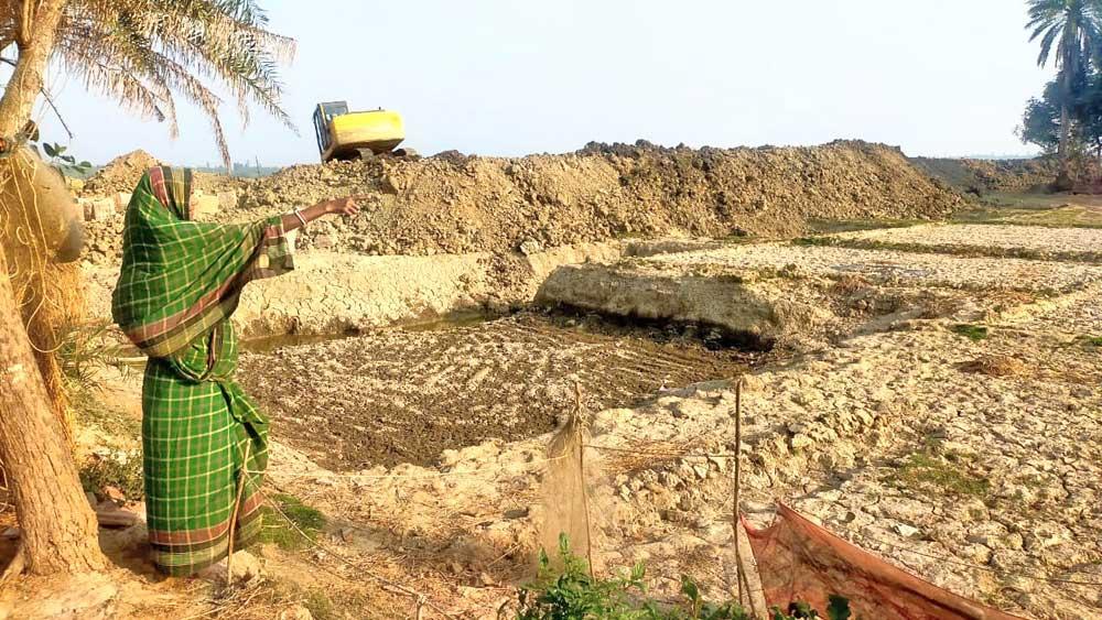 ওইখানে...:বাঁধের কাজ যেখানে চলছে, সেখানেই ছিল জমি। শোলেমারি নদীর ধারে উত্তর গোপালনগর গ্রামে।
