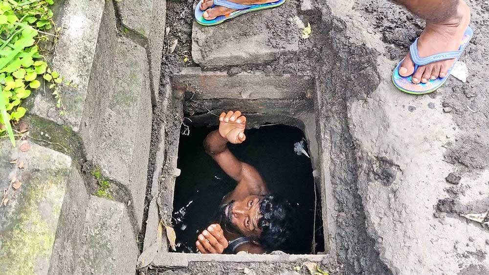 অব্যবস্থা: নিয়ম থাকলেও নেই তার প্রয়োগ। বিনা সুরক্ষায় ম্যানহোলে নেমে কাজ করছেন এক সাফাইকর্মী।