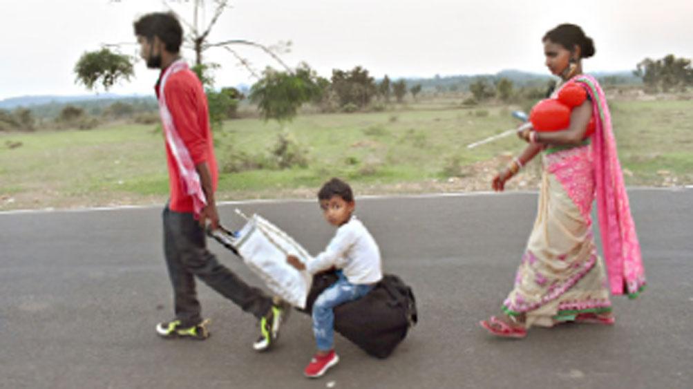 নিরুপায়: স্ত্রী-ছেলেকে নিয়েই হেঁটেই বাড়ির পথে।  বান্দোয়ানের চান্দড়া গ্রামের কাছে। ছবি: রথীন্দ্রনাথ মাহাতো