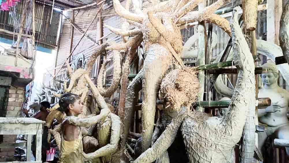 রোজগারে: প্রতিমা তৈরির কাজে সহযোগিতা রাহুলের।