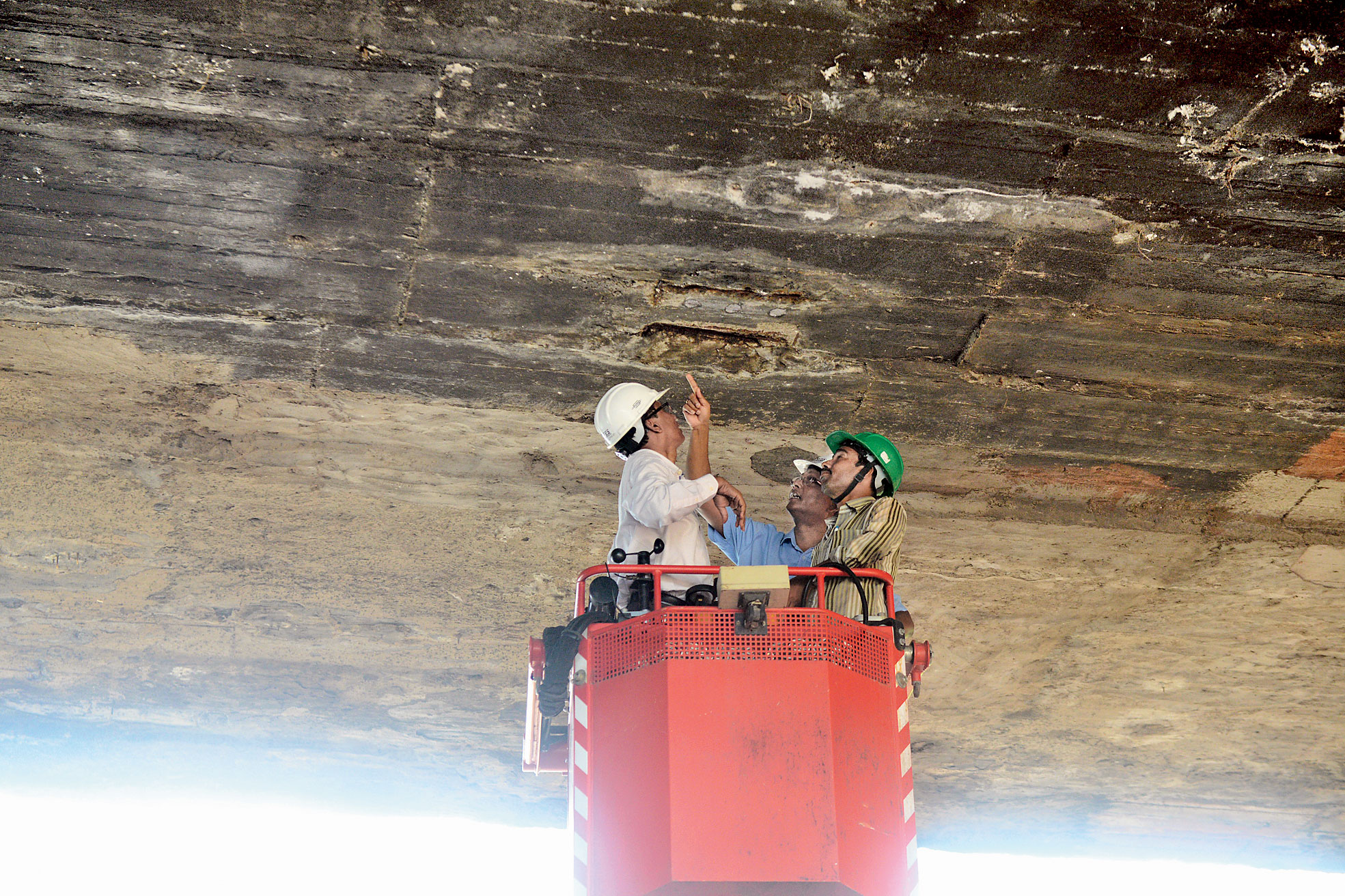 Engineers inspect the worn-out underbelly of the Tallah bridge on Saturday