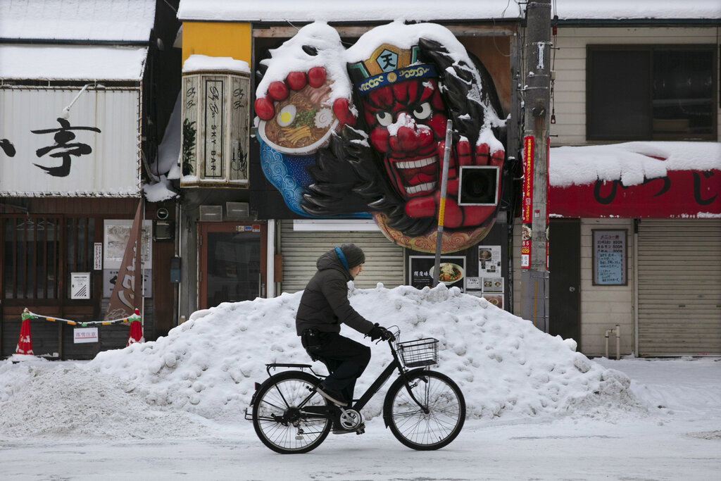 A man rides his bike as snow is pile up in front of a ramen restaurant in Sapporo, Hokkaido