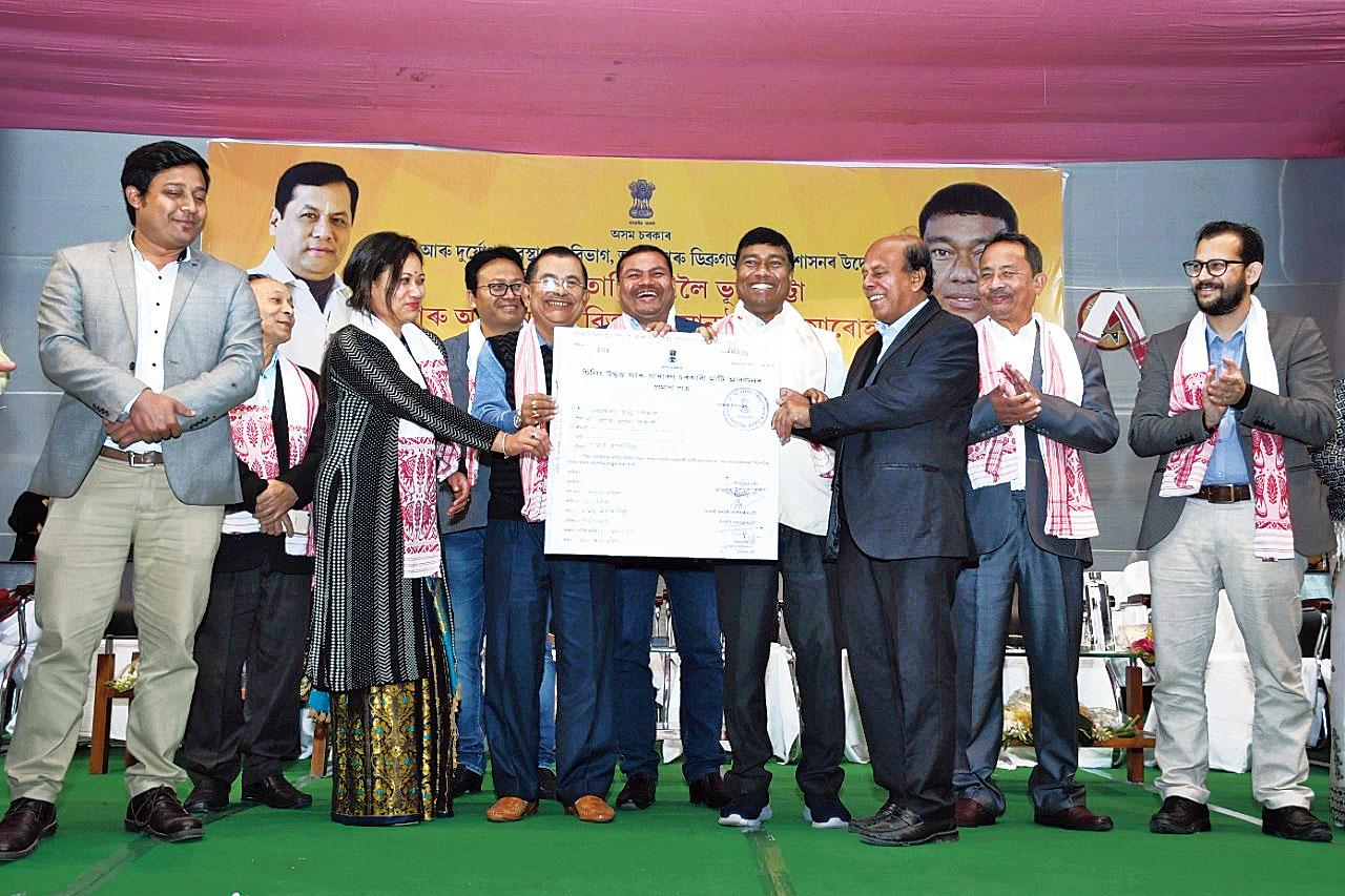 Rameswar Teli hands over a land patta to a beneficiary.