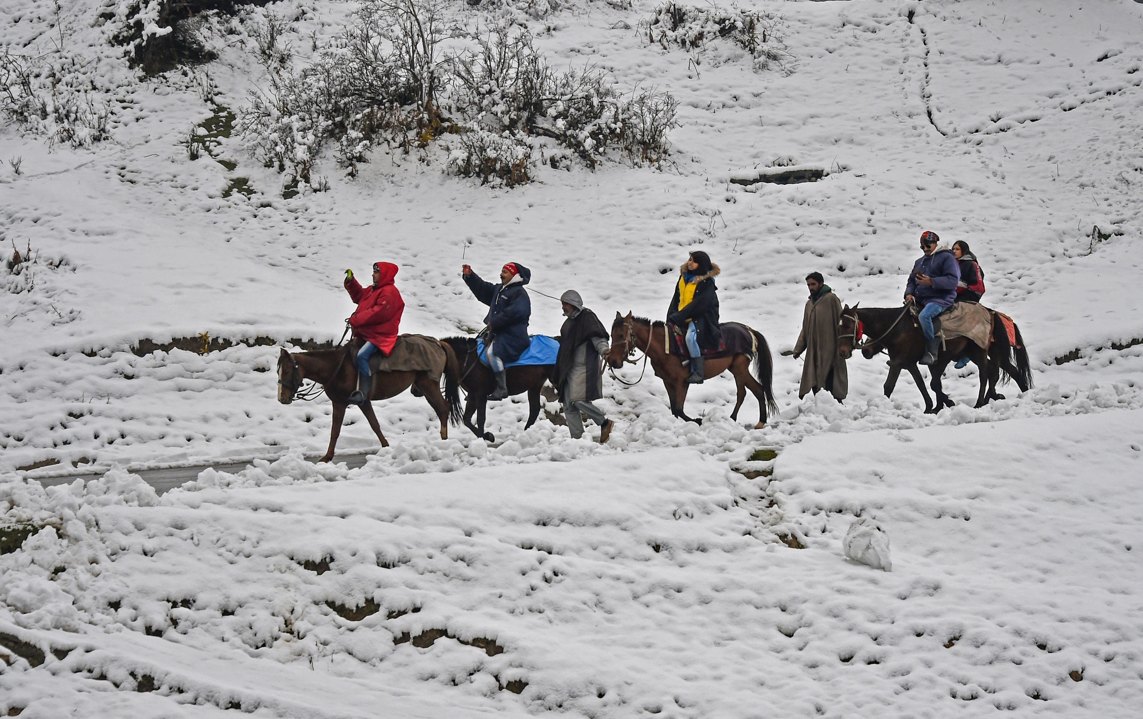 Tourists on a pony ride after the season's first snowfal in Gulmarg.