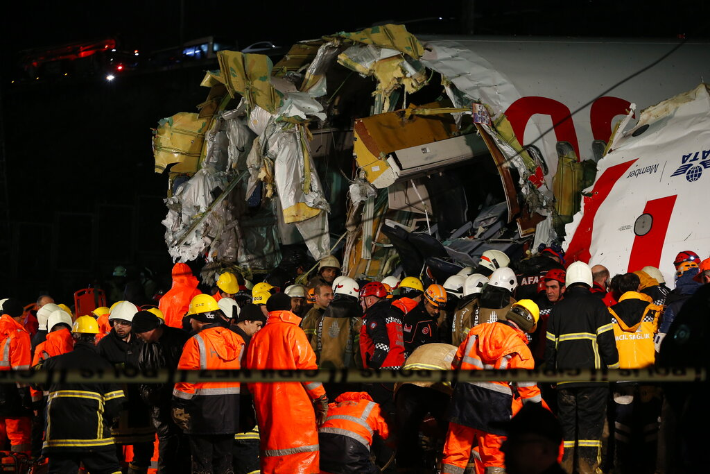 Rescue members and firefighters work after a plane skidded off the runway at Istanbul's Sabiha Gokcen Airport, in Istanbul, on Wednesday
