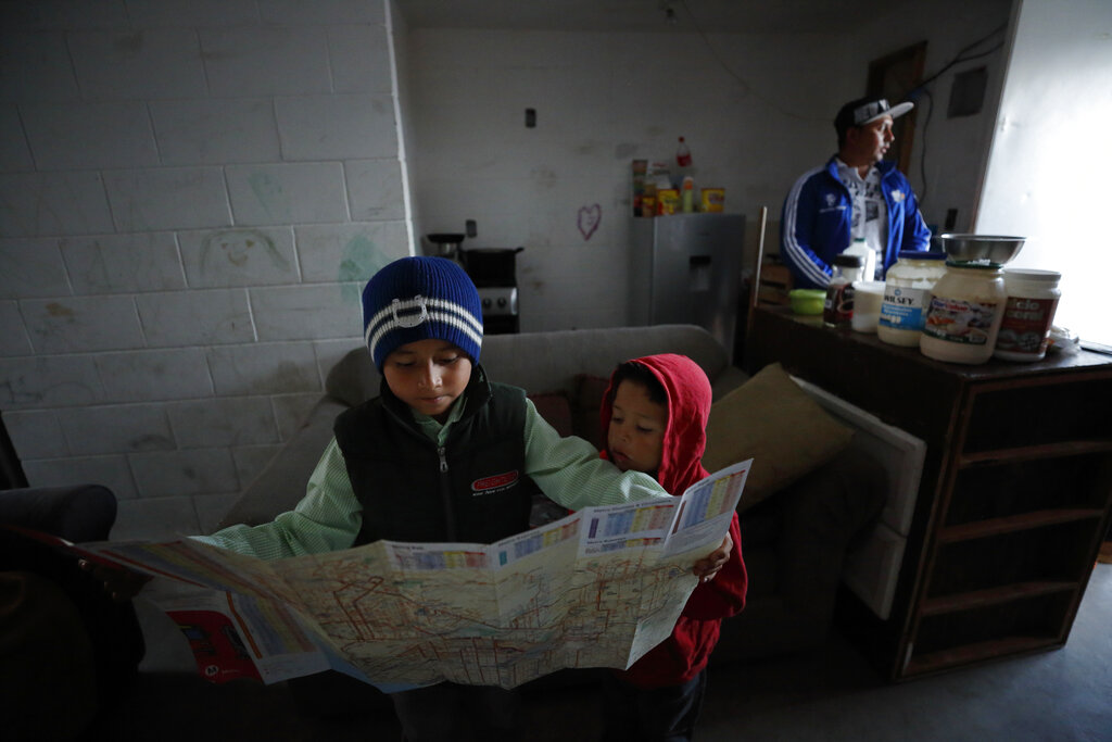 Nahum Perla, left, studies a San Diego map with his younger brother, Carlos Isai Perla, as their father, Juan Carlos Perla, right, gets ready to make the journey from their home on the outskirts of Tijuana, Mexico, to San Diego for an asylum hearing