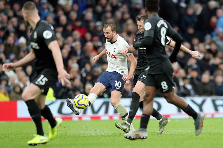 Tottenham's Harry Kane, center, kicks the ball during the English Premier League soccer match between Tottenham Hotspur and Brighton & Hove Albion at the Tottenham Hotspur Stadium in London, England