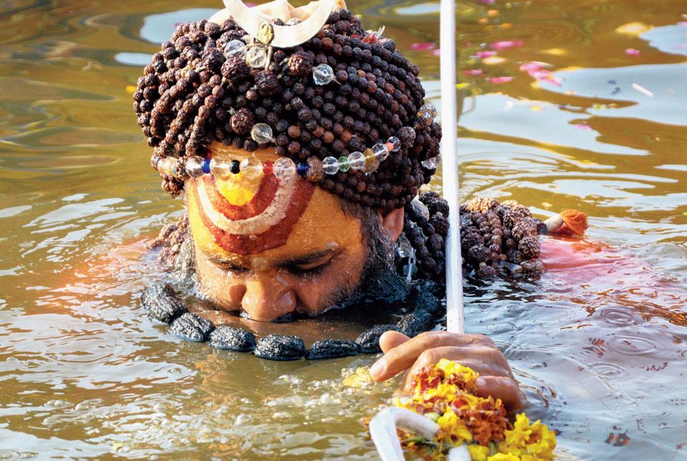A sadhu takes a holy dip at Sangam during Kumbh Mela in Prayagraj.