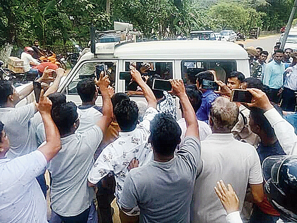 A crowd gathers around Sanaullah's car in Goalpara on Saturday.