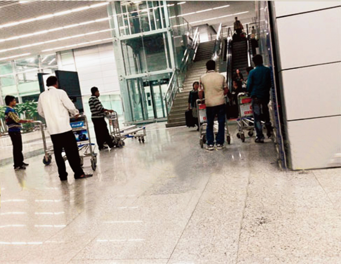 Trolley retrievers masquerading as passenger assistance staff (published in Metro on January 6, 2015) in the international arrival lounge of Calcutta airport