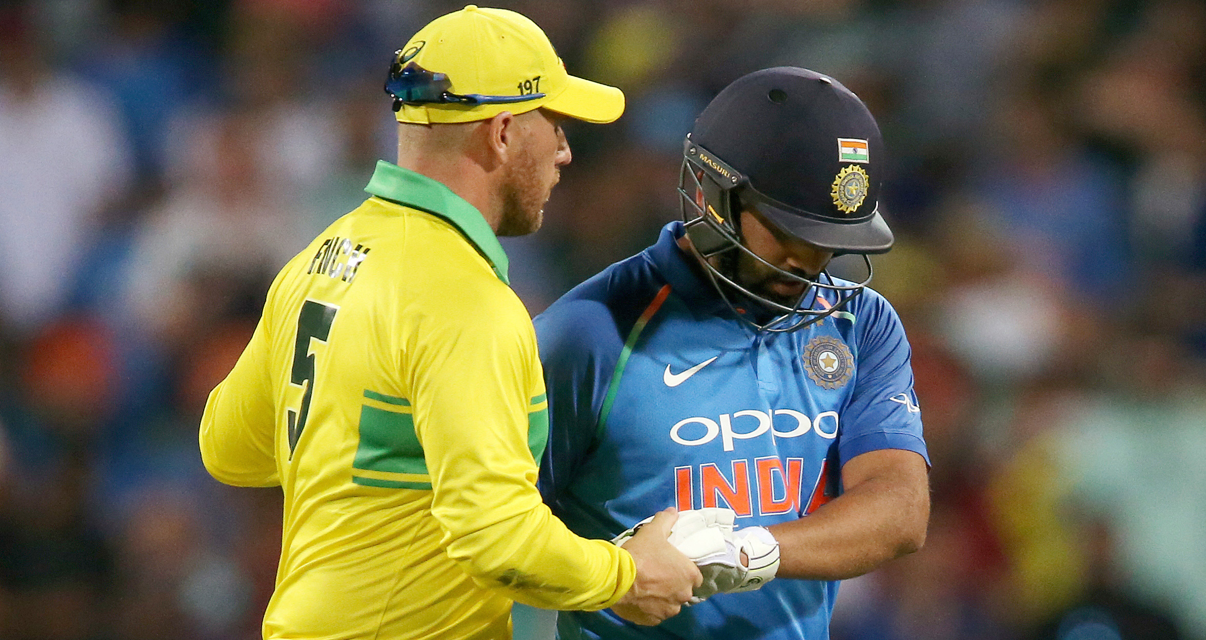 Australia's Aaron Finch, left, shakes hands with India's Rohit Sharma, right, after he was caught out against during their one day international cricket match in Sydney on Saturday, January 12, 2019.