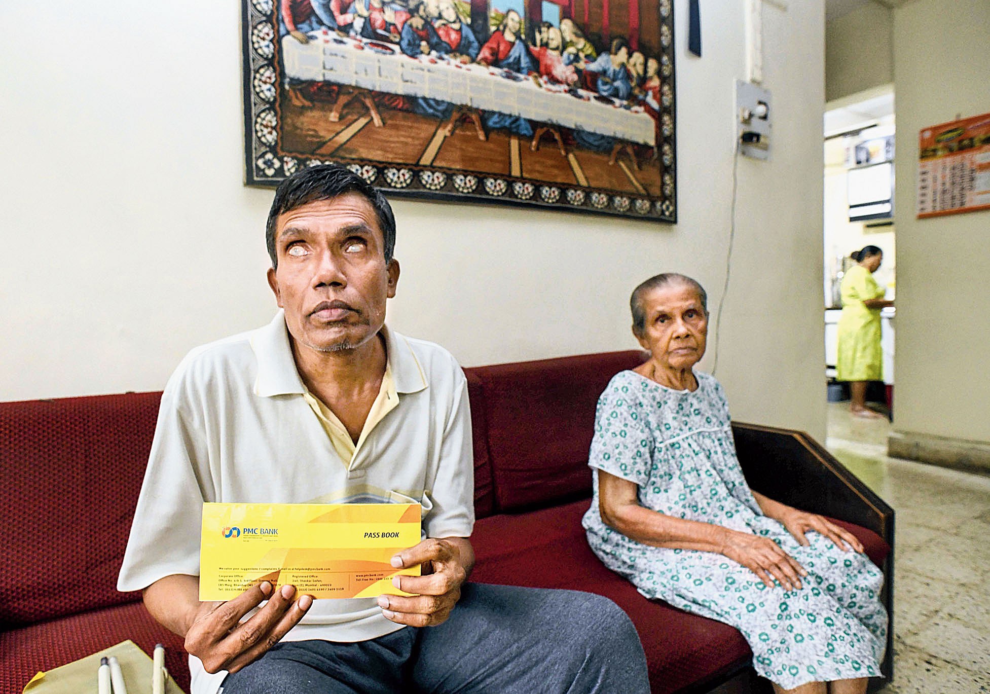 Allwyn Dsouza, 100 per cent blind for the past 20 years, depends on the interest from his deposit in PMC Bank for looking after himself and his 85-year-old mother Tresea (right)