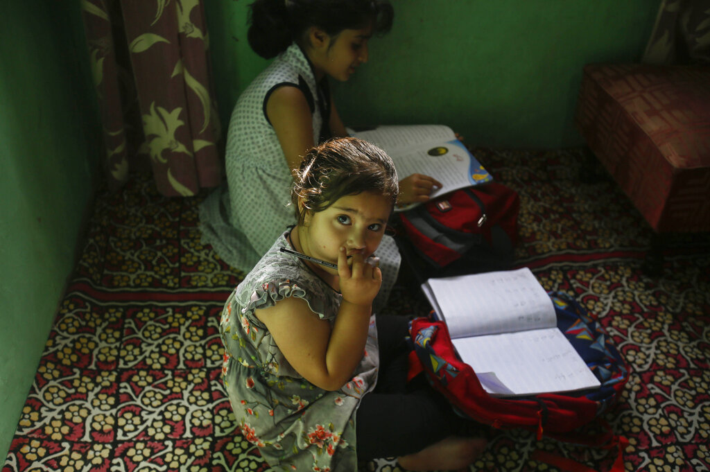 A girl reacts to camera as children attend private classes at a teacher's residence in Srinagar, Kashmir, on Wednesday, Aug. 28, 2019.