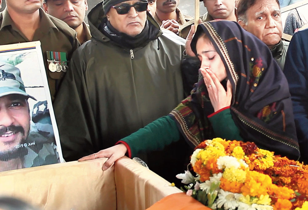 Nikita Kaul touches the coffin of her husband, Major Vibhuti Shankar Dhoundiyal, during his funeral in Dehradun on Tuesday.