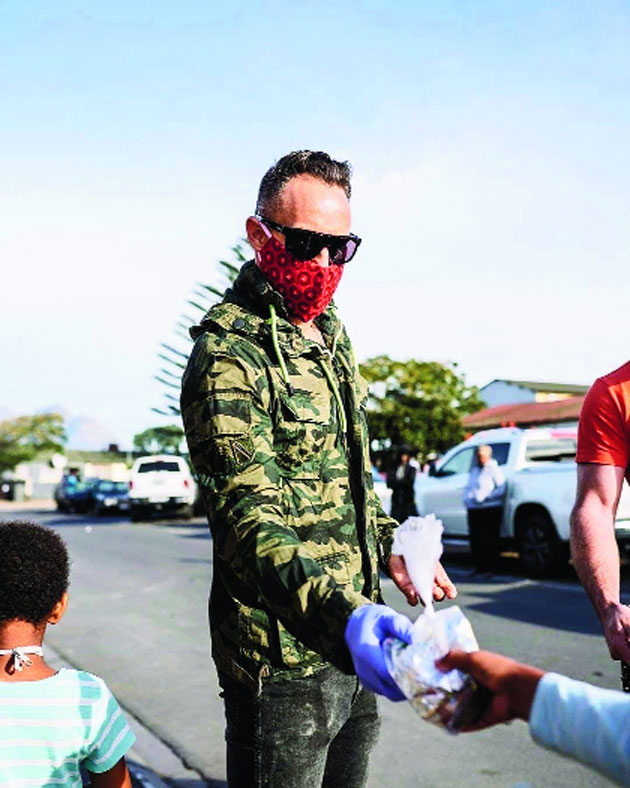 Former South Africa cricket captain Faf du Plessis distributes food in Cape Town.