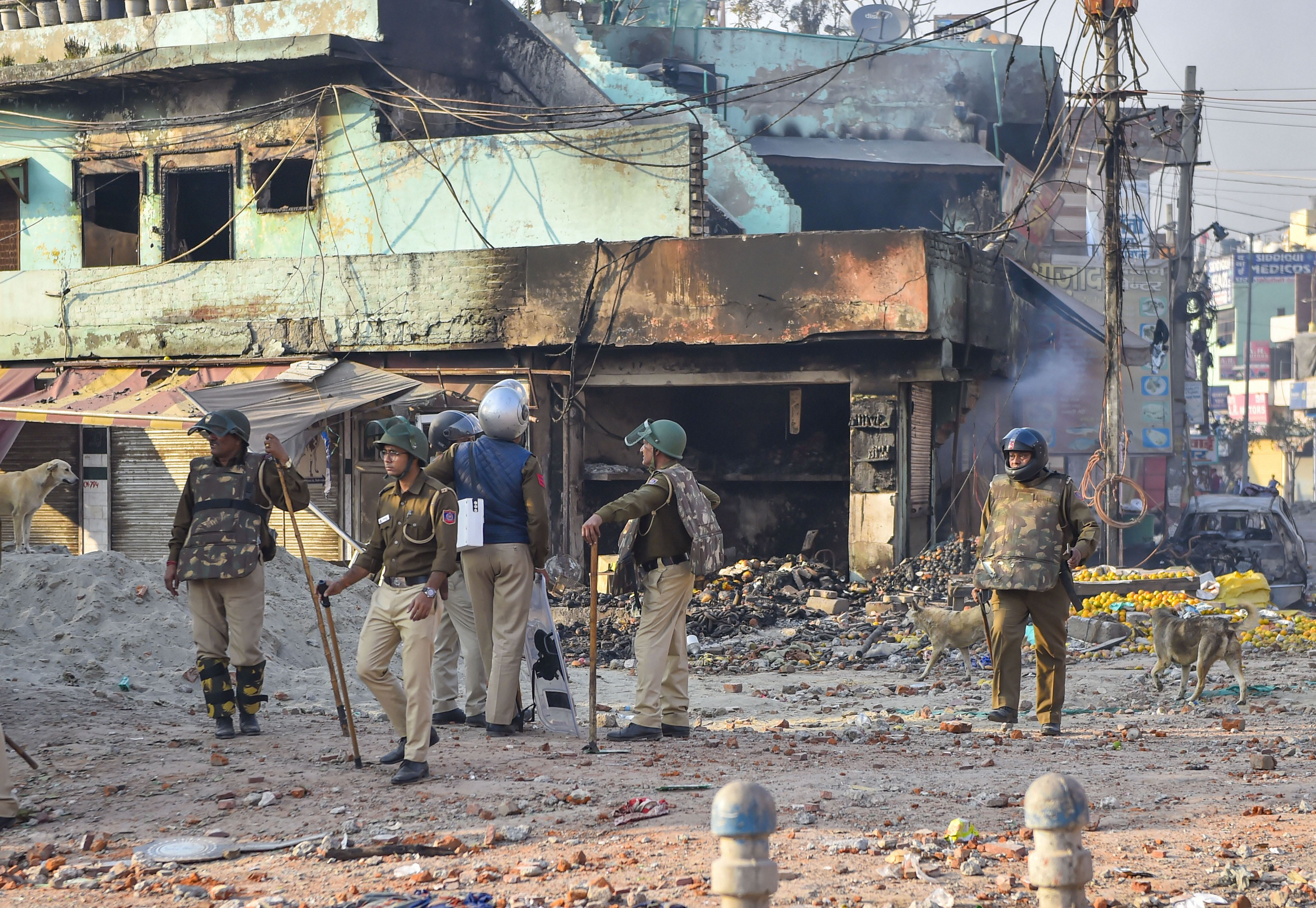 Security personnel stand guard near a neighbourhood vandalised by rioters during clashes between those against and those supporting the Citizenship (Amendment) Act in north east Delhi, Tuesday, February 25, 2020