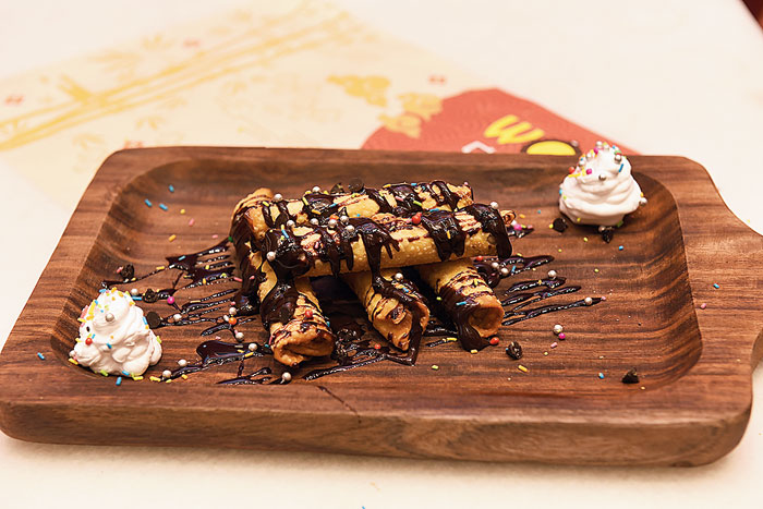 Molten Chocolate Spring Roll is the dessert variant of spring rolls, decorated with molten chocolate and is a mix of sweet and savoury.  Rs 229