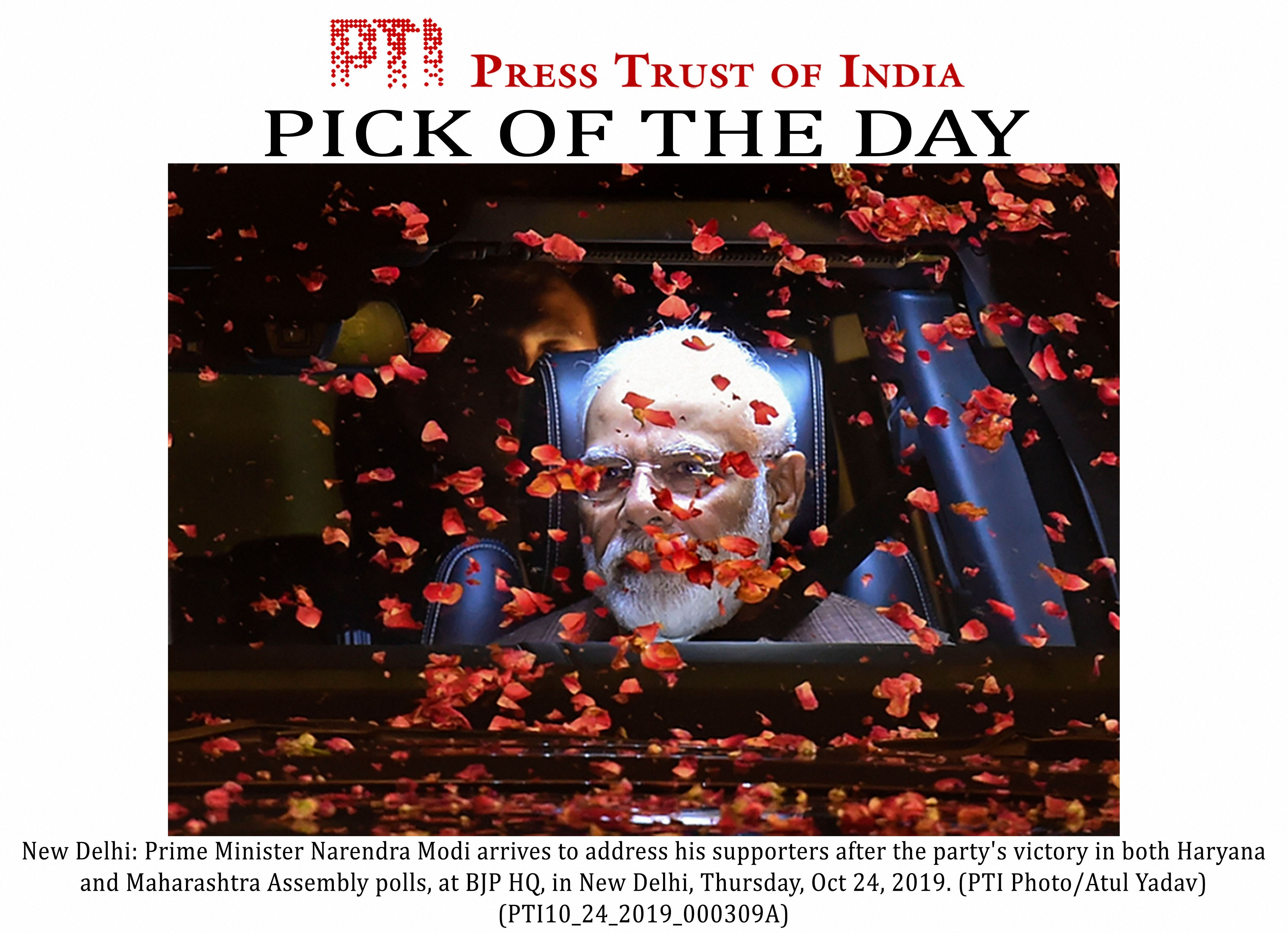Petals are showered as Prime Minister Narendra Modi arrives to address supporters at the BJP headquarters in New Delhi on October 24.